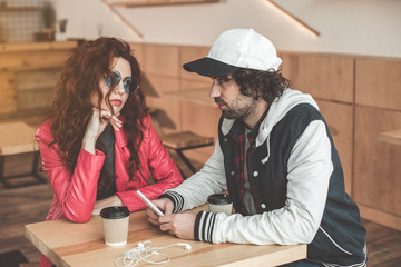 Young man and woman are looking at each other with seriousness while sitting in cafeteria. Guy is holding smartphone
