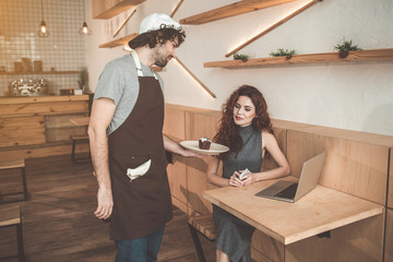 Here is your order. Polite man is serving food to customer. Woman is looking at cake with appetite while sitting at table near laptop