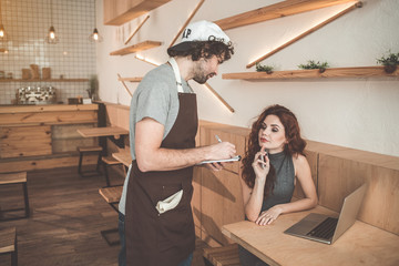 Cheerful waiter is receiving an order in young pensive lady. He is listening to client with attention and making notes