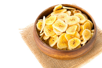 Heap of dried banana chips snack in wooden bowl over white