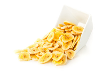 Heap of dried banana chips snack in white bowl over white