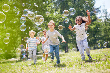 Multi-ethnic group of little friends with toothy smiles on their faces enjoying warm sunny day while participating in soap bubbles show Wall mural