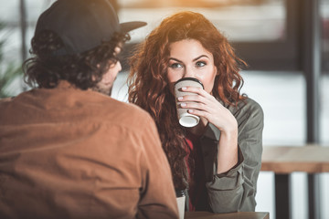 Portrait of cheerful young woman enjoying talk with her boyfriend in cafe. She is drinking cup of coffee while sitting at table