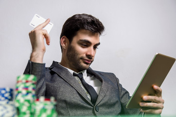 Man holding card ace and digital tablet, poker chips in foreground. Online poker