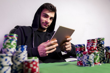 Casual man with hood playing online poker at home via digital tablet