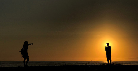 A man takes a photo of a woman on a beach at sunset in Lima