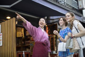 店員に道を教えてもらう外国人観光客