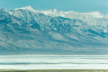 Mount Whitney with snow and a salt pond below in the foreground