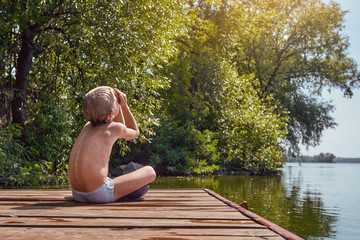 Little boy on the pier having rest and looking on sun