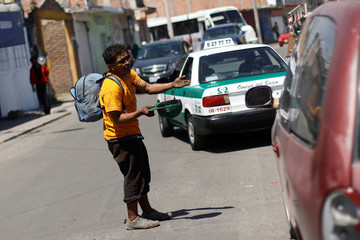 A Central American migrant, moving in a caravan through Mexico, asks for money after disembarking from a freight train in Irapuato