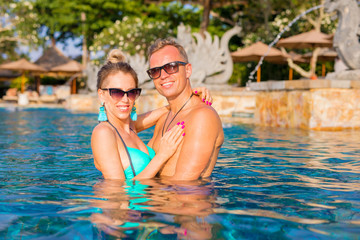 Couple enjoying swimming pool in luxury resort