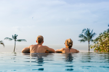 Couple in infinity pool looking at horizon