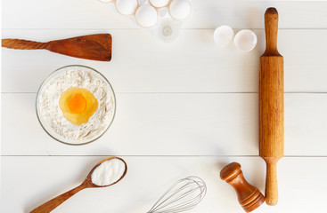 Process of baking, cooking. Flour in glasswares with a yolk on a white wooden table. Eggs in packing, rolling pin, wooden shovel and a spoon with sugar. Top view, copy space