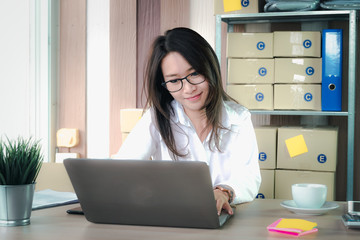 Asian beautiful young business woman owner of the SME start up company are get purchase orders from customers in the online trading business with a computer laptop in the Home Office