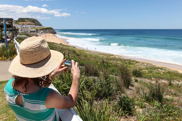 Tourist taking photo at Bar Beach - Newcastle Australia. Newcastle a couple of hours north of Sydney is becoming a popular destination.