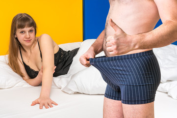 Woman in bed and man in underwear - impotence concept
