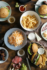 Outdoor table with burger, french fries, salad and snacks on wooden table with beer, top view. Outdoors food Concept
