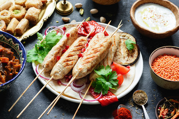 Shish kebab, meat skewers or shashlik garnished with parsley, pomegranate seeds and grilled vegetables