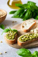 Pesto bruschetta on wooden board. Selective focus. Traditional italian antipasto