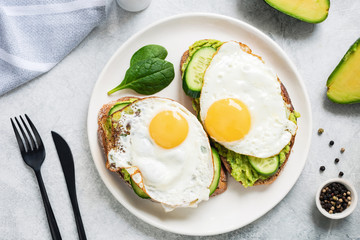 Two toasts with sunny side up egg, avocado and cucumber on white plate, top view. Healthy breakfast