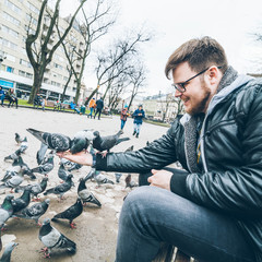 young man feed doves in city park.