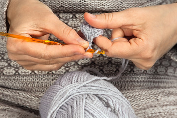 hands knitting with crochet hook and grey yarn