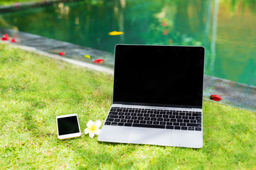 Laptop computer and mobile phone in grass by the pool