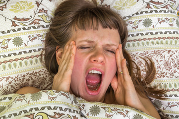 Attractive young woman is yawning in bed after sleeping