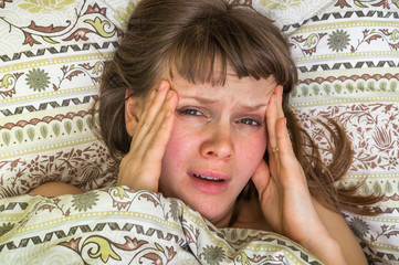 Young woman in bed having headache in the morning