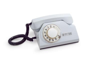 Old telephone set with rotary dial in white plastic housing
