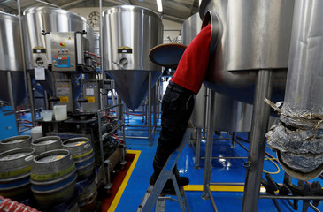 A worker cleans a mash tun at the Windsor and Eton brewery in Windsor