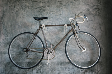 Antique bicycle on grunge gray wall