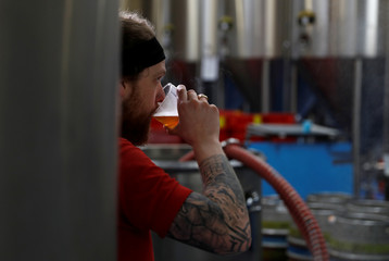 A worker tastes the liquid from a mash tun at the Windsor and Eton brewery in Windsor