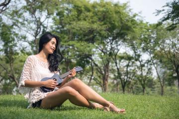 woman play on Ukulele in garden