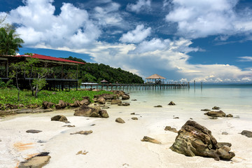 Tropical landscape of rocky beach with turquoise clean water and pier in the distance and blue sky. Saracen Bay, Koh Rong Samloem. Cambodia, Asia.