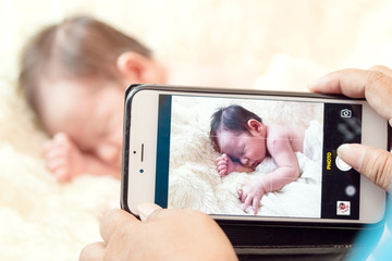 Woman taking picture of sleeping baby with smartphone. Focus on smartphone
