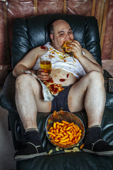 Overweight man eating and watching TV