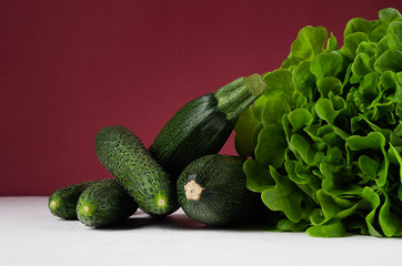 Dark colorful green vegetables on white table and bordo wall. Summer fashion food background.