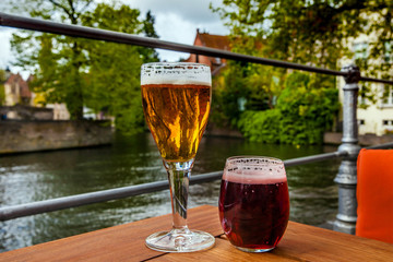 Wall Murals Bridges Two glasses of belgian beer standing on the table with Bruges city view