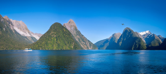 A small boat in the morning at Freshwater Basin in Milford Sound with Mitre Peak and numerous other Mountain Cliffs in Fiordland National Park, New Zealand, South Island.
