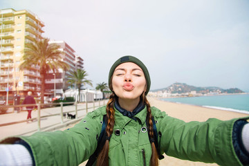 Pretty young female tourist takes travel selfie at the beach while spring vacation Barcelona in Spain.Beautiful young brunette making selfie sending cute air kiss.Beautiful young travel blogger.