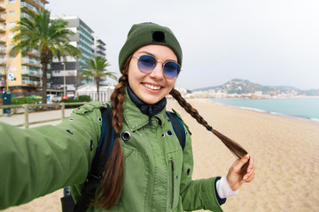 Pretty young female tourist takes travel selfie at the beach while spring vacation Barcelona in Spain.Beautiful young travel blogger.Close up sunny portrait of young happy girl making selfie and smile