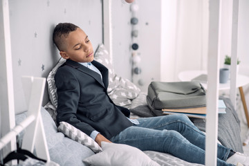 Difficult learning. Depressed afro american boy closing eyes while sitting on bed at home