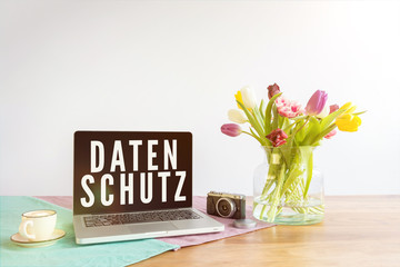 Laptop with Datenschutz writing in german meaning data privacy in english on wooden desk with white background