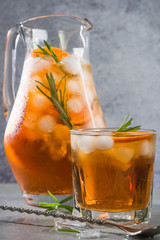Ice cold tea in pitcher and glass with rosemary garnish