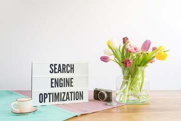 Light box with search engine optimization writing on wooden desk with white background