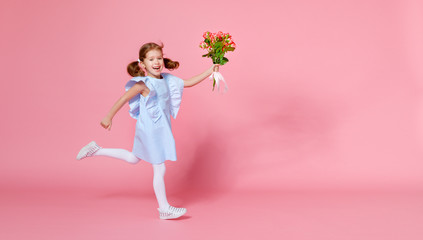 funny child girl runs and jumps with bouquet of flowers on colored background