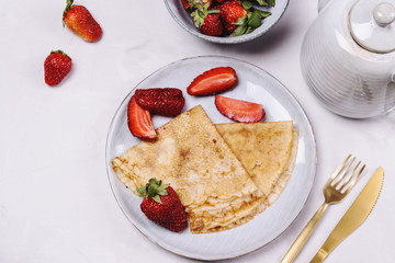 Openwork thin cheese crepes served with strawberry on grey concrete background. Homemade pancakes. Delicious breakfast