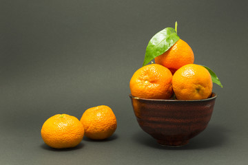 Still life studio shot of a red ceramic bowl with black texture filled with fresh orange tangerines on gray background.