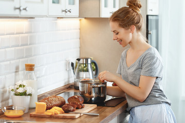 young woman in pajamas prepares breakfast in morning